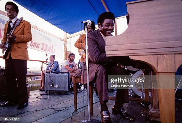 American RB musician Fats Domino plays piano as he performs onstage during the New Orleans Jazz Heritage Festival at the Fair Grounds Race Course New...