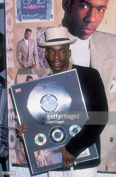 American R&B singer Bobby Brown holding a copy of his album 'Don't Be Cruel', at the HMV shop, circa 1988.