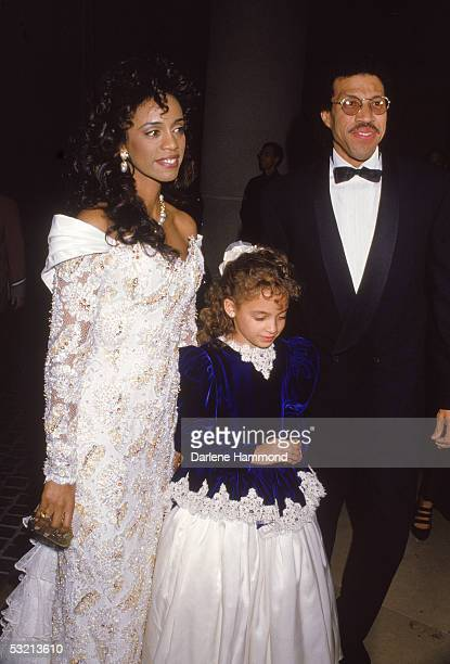 American R&B singer Lionel Richie arrives at a formal event with his wife Brenda and their daughter Nicole, late 1980s.