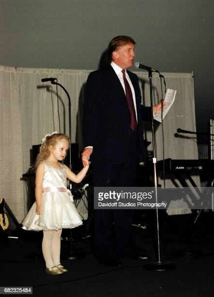American real estate developer Donald Trump holds hands with his daughter Tiffany as he speaks from the stage at the MaraLago club Palm Beach Florida...