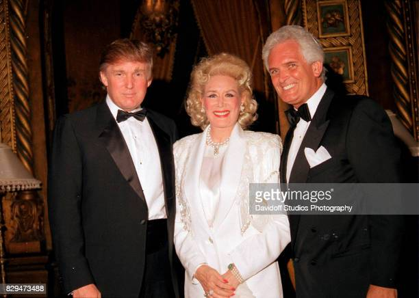 American real estate developer Donald Trump poses with British philantropist Celia Lipton Farris and businessman Bert Sokol during the official...