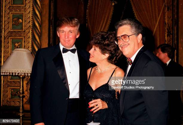 American real estate developer Donald Trump poses with married insurance executives Robin and Richard Bernstein during the official opening of the...