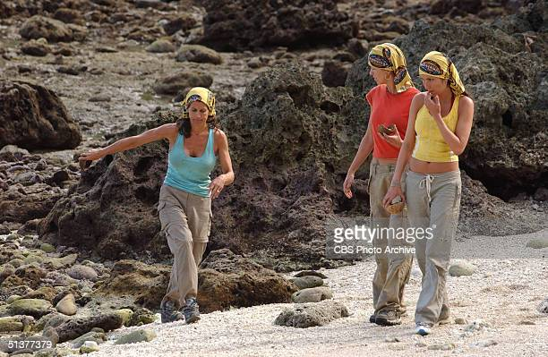 American reality show contestants and ersatz castaways Lisa Keiffer Mia Galeotalanza and Julie Berry walk by the rocks on the beach during the second...