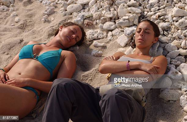 American reality show participants and simulated castaways Ami Cusack and Eliza Orlins lie on the beach with their heads resting on rocks during the...
