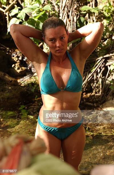 American reality tv show contestant Ami Cusack dressed in a blue twopiece bikini stands in the shade with her hands behind her head during an episode...