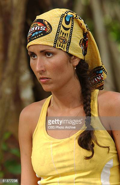 American reality tv show participant Julie Berry dressed in a yellow tank top and matching yellow 'Survivor' scarf stands and watches during an...