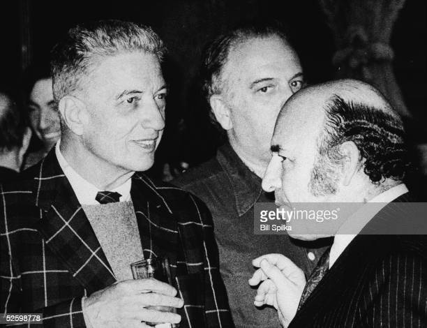 American record producer musician and music critic John Hammond holds a glass and talks to jazz impresario George Wein at a party 1970s