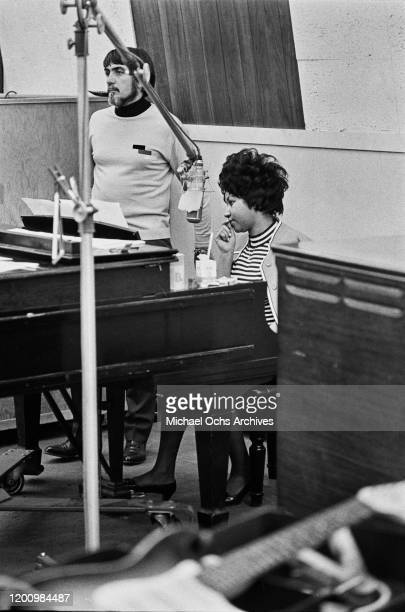 American recording engineer and producer Tom Dowd with American singer, songwriter, pianist, and civil rights activist Aretha Franklin sitting at the...
