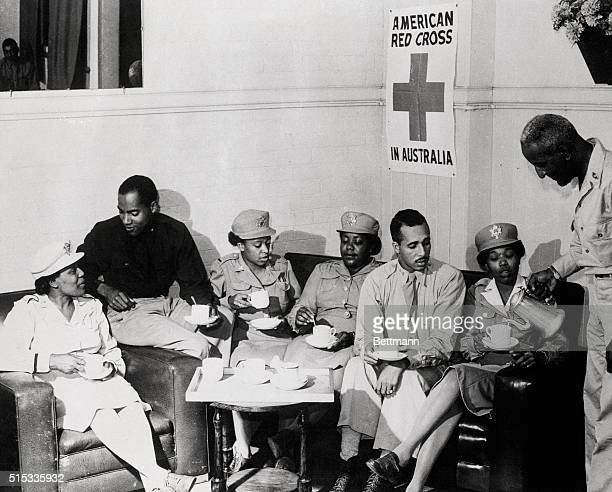 American Red Cross club director Harvey Shaw of Philadelphia PA pours out coffee for US Army nurses and officers serving in the Southwest Pacific...