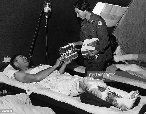 American Red Cross hospital field director Barbara J Maxwell gives a Red Cross comfort kit to injured Sergeant William C Mullen who lies in a cot...