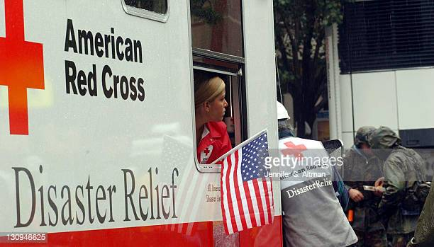American Red Cross worker holds an American Flag and looks in disbelief as she heads down toward the wreckage of the World Trade Center after...