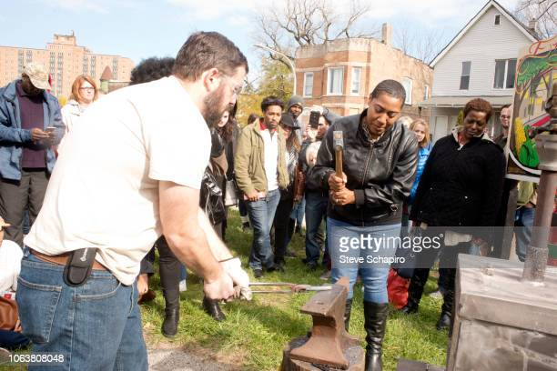 American religious activist and blacksmith Michael Martin of the RAWTools organization holds a part of a rifle against an anvil as Residents...