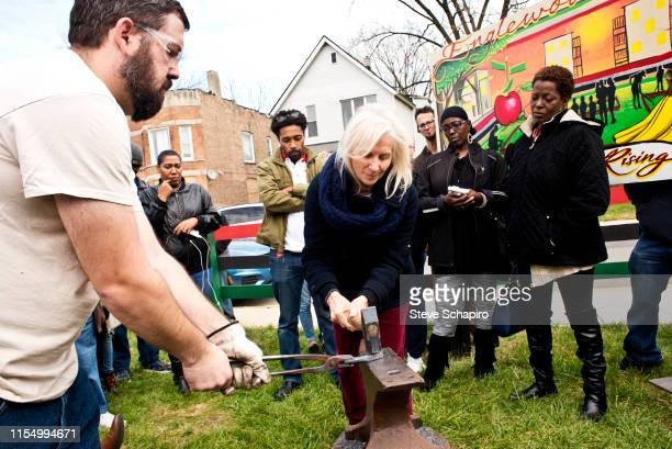 American religious activist and blacksmith Michael Martin of the RAWTools organization holds a part of a rifle against an anvil as Maura Smith wields...