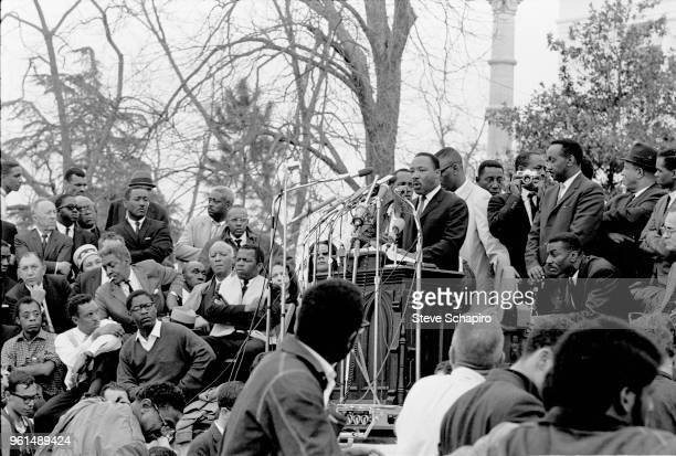 American religious and Civil Rights leader Dr Martin Luther King Jr speaks from a pulpit in front of the Montgomery State Capitol building at the...