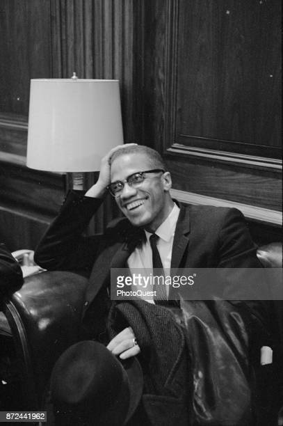 American Religious and Civil Rights leader Malcolm X laughs as he sits in an armchair before a press conference Washington DC March 26 1964