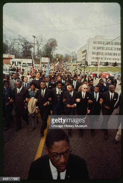 American religious and Civil Rights leader Martin Luther King Jr leading a procession of people to demonstrate against police treatment of voter...