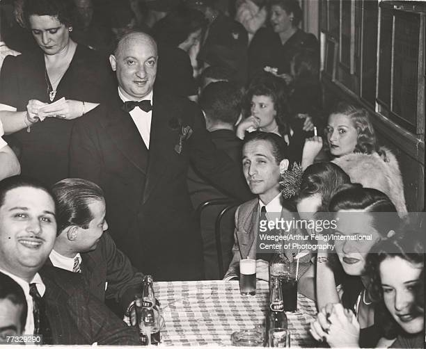 American restauranteur and social activist Sammy Fuchs poses with patrons at his establishment Sammy's on the Bowery New York New York mid 1940s...