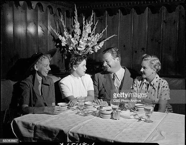 American restauranteur Bernard Toots Shor and actress and songwriter Margaret Whiting sit with two unidentifed women in Shor's restaurant New York...