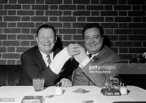 American restauranteur Bernard Toots Shor and American actor and entertainer Jackie Gleason smile as they clasp their castcovered hands in Shor's...