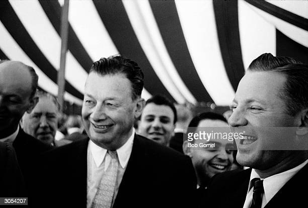 American restauranteur Bernard Toots Shor and former baseball player Ed Lopat laugh under a striped tent at the groundbreaking ceremony of Shor's new...