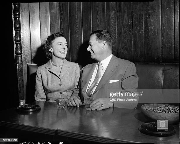 American restauranteur Bernard Toots Shor shares a laugh and a drink with Evelyn Seibold in a woodpanelled booth at his restaurant New York New York...