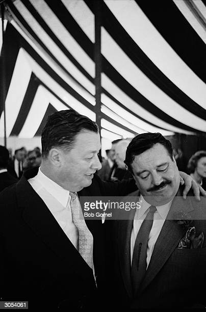 American restauranteur Bernard Toots Shor stands with his arm around the shoulders of American actor and comedian Jackie Gleason as the pair stand...