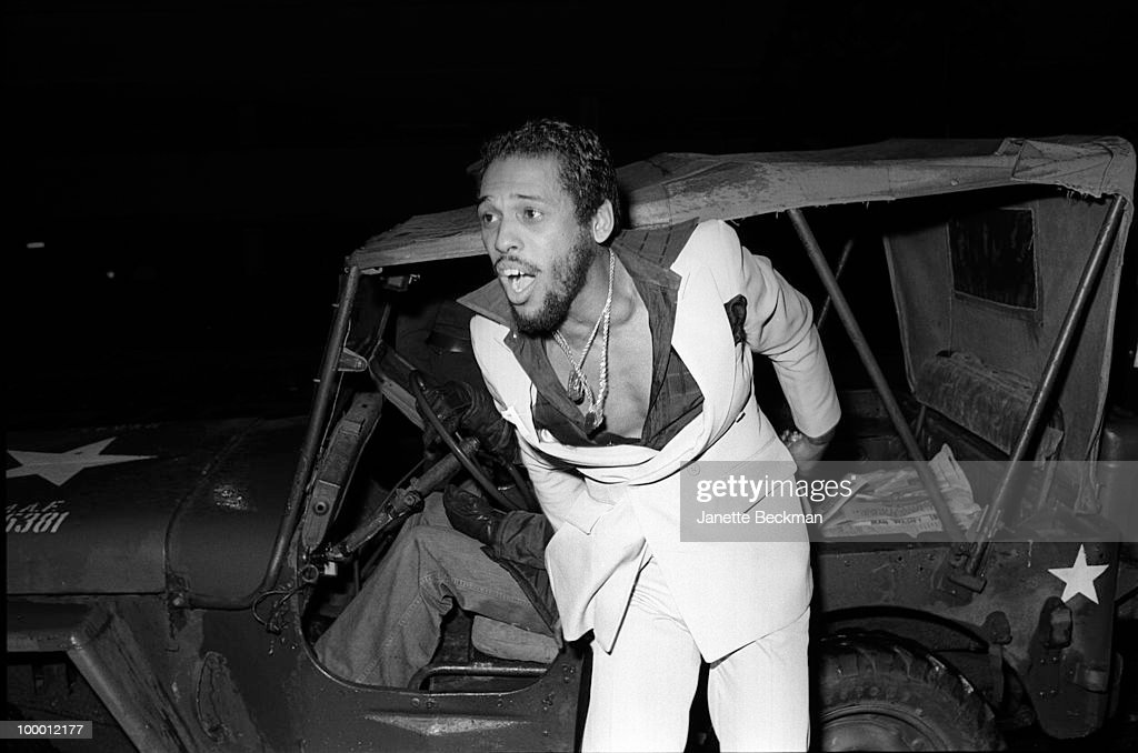 American rhythm and blues musician John Whitehead (1949 - 2004), of the duo McFadden & Whitehead, steps out of a military jeep, England, mid 1979.