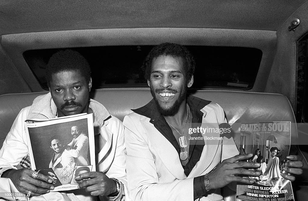 American rhythm and blues musicians Gene McFadden (1948 - 2006) (left) and John Whitehead (1949 - 2004), together known as McFadden & Whitehead, sit in the back of a car and hold up the June 19, 1979, issue of 'Blues & Soul (& Disco Music Review),' the cover of which mentions an article about them, England, mid 1979.