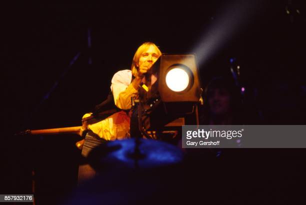 American Rock and Pop musician Tom Petty aims a spotlight as he leads his band the Heartbreakers during a performance on the 'Long After Dark' tour...