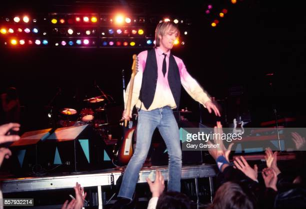 American Rock and Pop musician Tom Petty shakes hands with fans as he leads his band the Heartbreakers during a performance on the 'Long After Dark'...