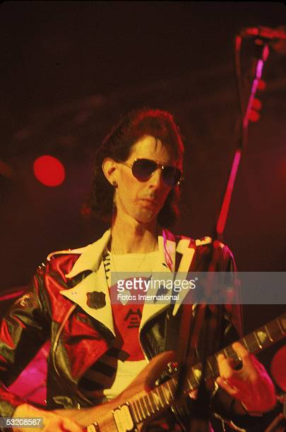 American rock and roll musician and producer Ric Ocasek , plays guitar on stage, late 1980s.