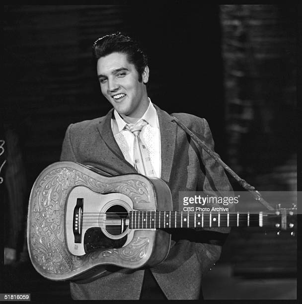 American rock and roll singer and actor Elvis Presley smiles as he stands with his hands in his pockets and a guitar around his shoulders during his...
