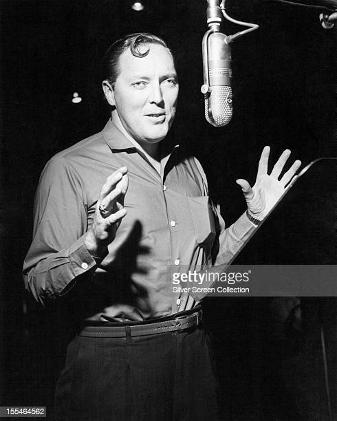 American rock and roll singer Bill Haley at a microphone circa 1955