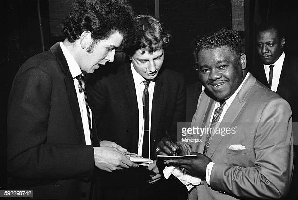 American rock and roll star Fats Domino signs autographs for fans on the stage of the Saville Theatre in London as he prepares for the evening show...