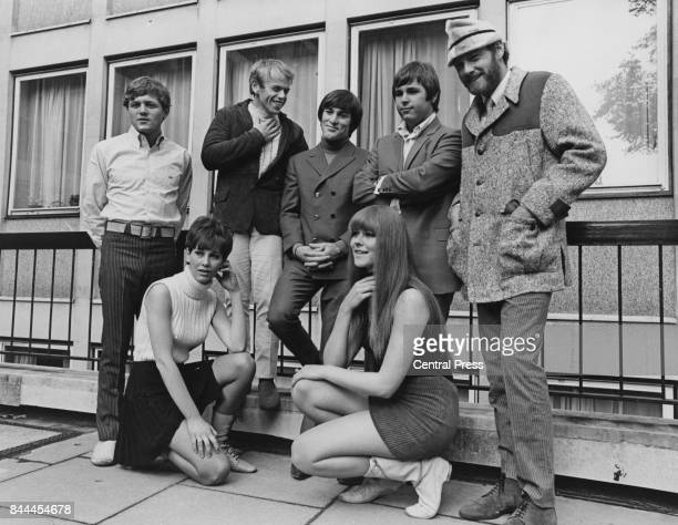 American rock band The Beach Boys pose outside EMI House in Manchester Square, with two young women, whilst in London for a concert tour, 7th...