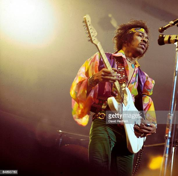 American rock guitarist and singer Jimi Hendrix performs live on stage playing a white Fender Stratocaster guitar with The Jimi Hendrix Experience at...