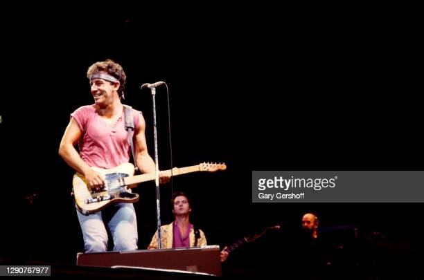 American Rock musician Bruce Springsteen plays guitar as he performs onstage, with the E Street Band, during the 'Born in the USA' tour, at Giants...