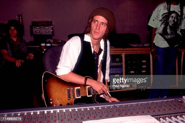 American Rock musician Izzy Stradlin holds his guitar as he sits at a mixing board during a studio session with his band, Izzy Stradlin and the Ju Ju...