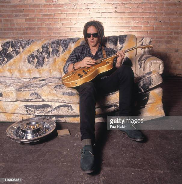 American Rock musician Izzy Stradlin of the band Izzy Stradlin and teh Ju Ju Hounds holds his guitar as he sits on a couch in a rehearsal space...