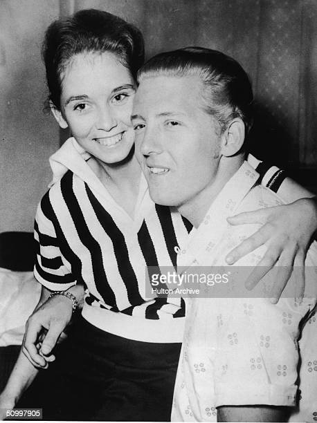 American rock musician Jerry Lee Lewis holds his second cousin and third wife Myra Brown in his lap at a press conference in the Westbury Hotel...