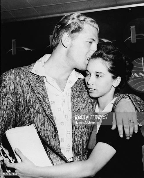 American rock musician Jerry Lee Lewis hugs his second cousin and third wife Myra Brown as they arrive in the airport from London after his tour of...