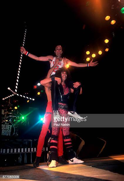 American Rock musician Kevin DuBrow sits atop the shoulders his bandmates Carlos Cavazo and Frankie Banali all of the band Quiet Riot as they perform...