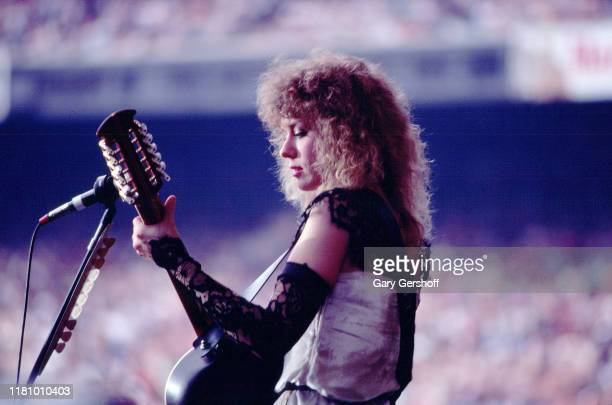 American Rock musician Nancy Wilson, of the group Heart, plays guitar as she performs onstage at Giants Stadium, East Rutherford, New Jersey, June...