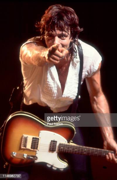 American Rock musician Rick Springfield plays guitar as he performs onstage at the Poplar Creek Music Theater, Hoffman Estates, Illinois, August 31,...