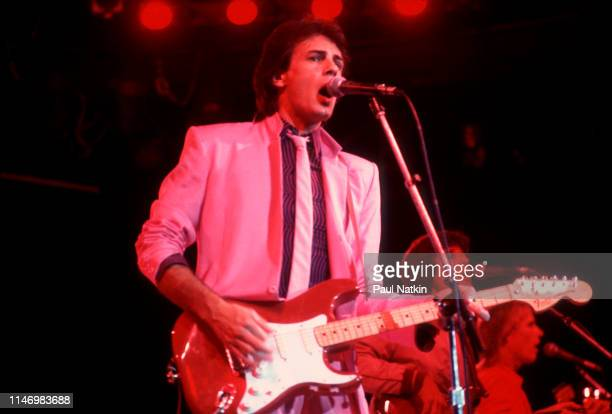 American Rock musician Rick Springfield plays guitar as he performs onstage at the Mill Run Theater, Niles, Illinois, September 6, 1981.