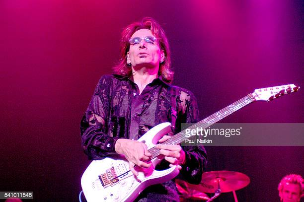 American rock musician Steve Vai plays guitar as he performs onstage, Chicago, Illinois, October 24, 2003. Behind him is drummer Jeremy Colson.