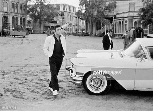 American rock n' roll singer and actor Elvis Presley walking past a Cadillac Eldorado on a movie set USA circa 1958