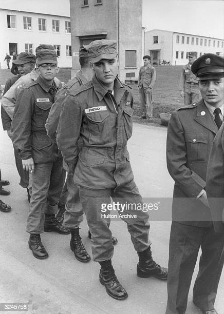 American rock n' roll singer and United States Army private Elvis Presley stands in line with other enlisted men and officers on a military base,...