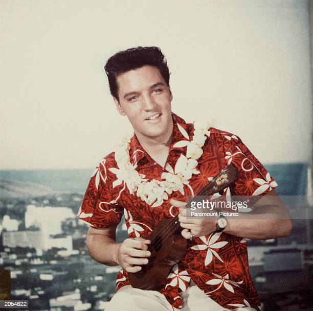 American rock n' roll singer Elvis Presley plays a ukelele wearing a Hawaiian shirt and lei in a still from the film 'Blue Hawaii' directed by Norman...