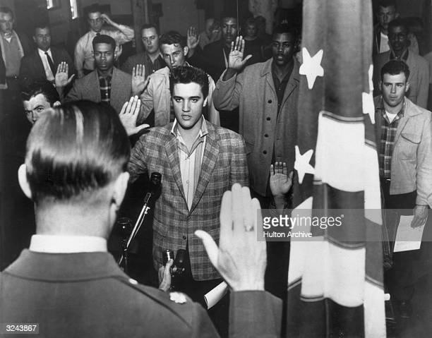 American rock n' roll singer Elvis Presley stands with a group of young men at an induction center, raising their right hands as they are sworn into...